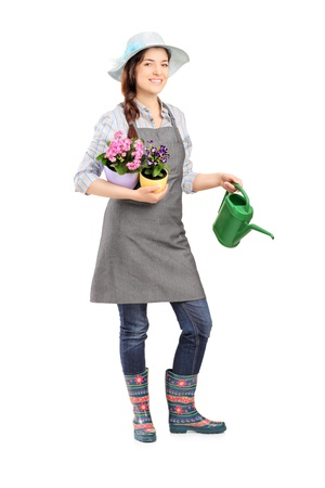 Full length portrait of a female gardener holding flower pots and watering can isolated on white background photo
