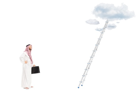 Full length portrait of a male arab person with suitcase standing in front of a ladder with cloud and looking, isolated on white background, shot with a tilt and shift lens photo
