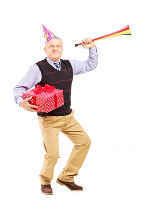 Full length portrait of a mature man wearing a party hat and holding a gift and horn isolated on white background photo