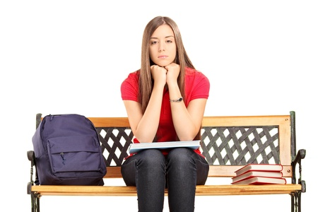 Unhappy female student sitting on a wooden bench isolated against white background photo