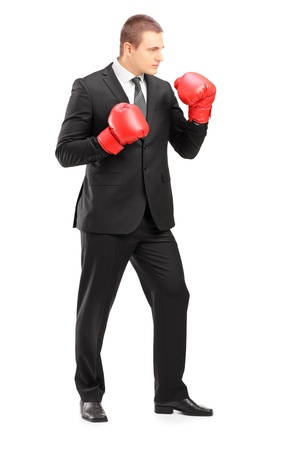 angry businessman: Full length portrait of a young businessperson in suit with red boxing gloves posing isolated on white background Stock Photo