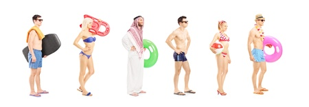 Full length portrait of young people with summer objects waiting in line isolated on white background, shot with a tilt and shift lens photo