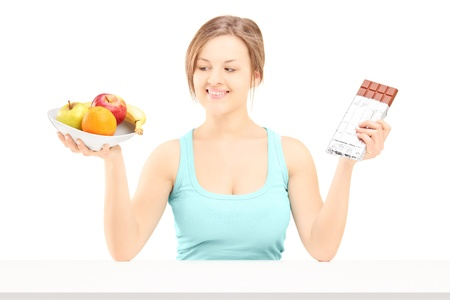 Young female holding a bowl of fresh fruit and chocolate, trying to decide which one to eat, isolated on white background  photo