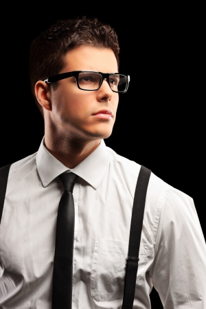 man with glasses: Fashionable young man with tie posing isolated against black background