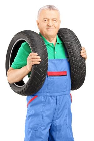 Mechanic holding a vehicle tires and looking at camera isolated on white background Stock Photo - 20785580