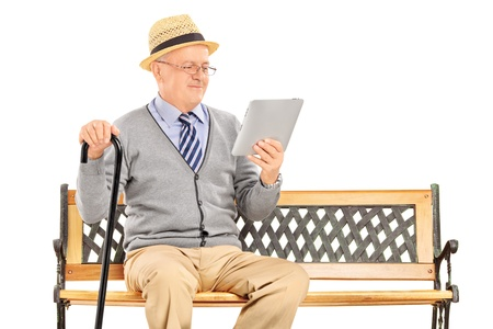 cane chair: Senior man sitting on a wooden bench and reading from a tablet isolated on white background Stock Photo