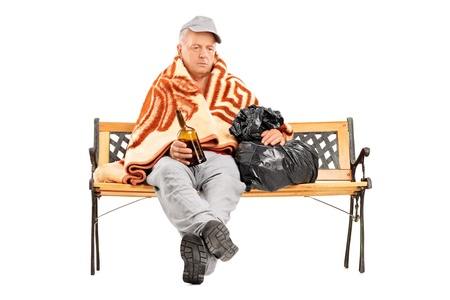 poorness: Drunk homeless mature man sitting on a bench and holding a bottle, isolated on white background Stock Photo