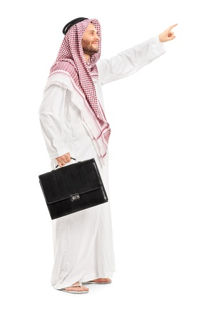 headcloth: Full length portrait of a male arab person holding a leather suitcase and pointing isolated on white background