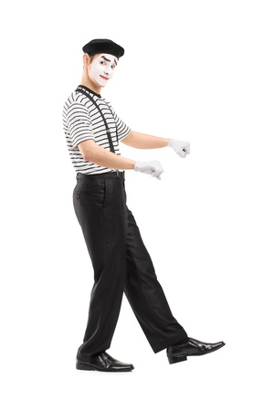 Full length portrait of a male mime artist performing isolated on white background