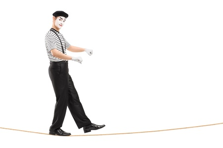 mimic: Full length portrait of a male mime artist walking on a rope and balancing, isolated on white background Stock Photo