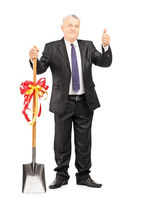 Full length portrait of a mature businessman holding a shovel with ribbon on it and giving thumb up isolated on white background photo
