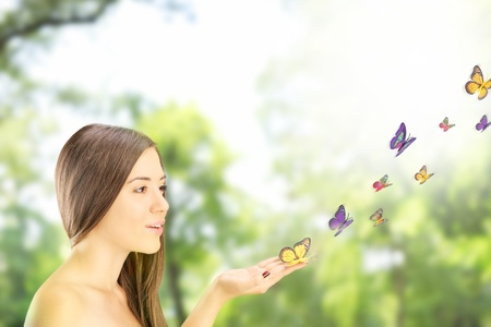 butterfly and women: Beautiful young female with many colorful butterflies on her hand, posing outside in a park