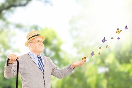 butterfly hand: Mature smiling man holding a cane and looking at many colorful butterflies outside in a park