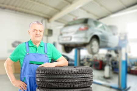 Auto mechanic posing on tires in front of car during automobile maintenance at auto repair shop Stock Photo - 20934226