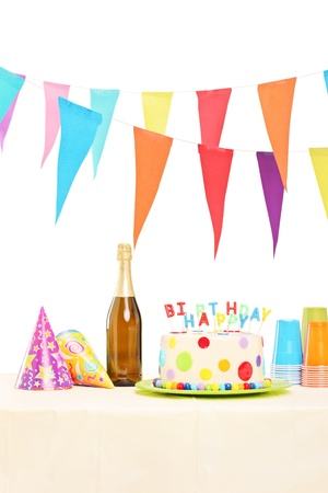 Bottle of sparkling wine, plastic glasses, party hats and birthday cake on a table, isolated on white background photo