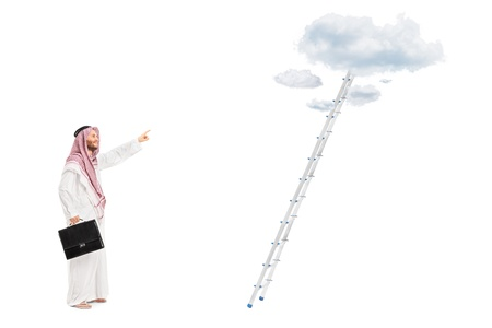 upwards: Full length portrait of a male arab person with briefcase standing in front of a ladder with cloud and pointing, isolated on white background, shot with a tilt and shift lens