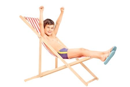 nackter junge: Happy Junge sitzt auf einem Stuhl im Freien mit erhobenen Händen auf weißem Hintergrund