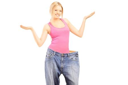 weightless: Hembra ingr�vido feliz con el viejo par de jeans que gesticula con las manos, aislados en fondo blanco