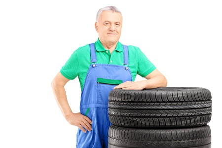 Smiling mature worker posing on car tires isolated on white background Stock Photo - 20934247