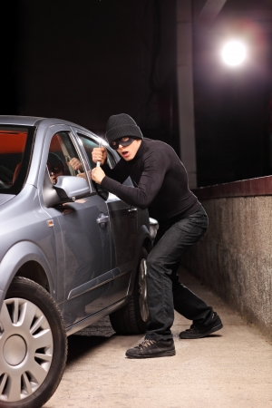 Thief with robbery mask trying to steal a car on a parking lot Stock Photo