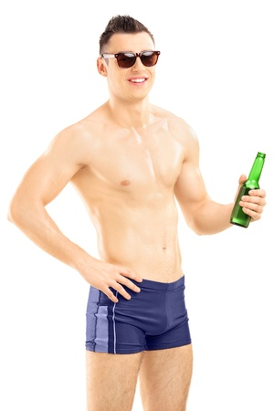 swimming shorts: Young handsome male in swimming shorts holding a beer bottle isolated on white background