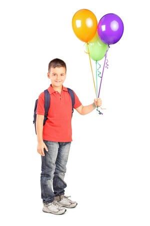 Full length portrait of a schoolboy with bag holding a bunch of balloons isolated on white background photo