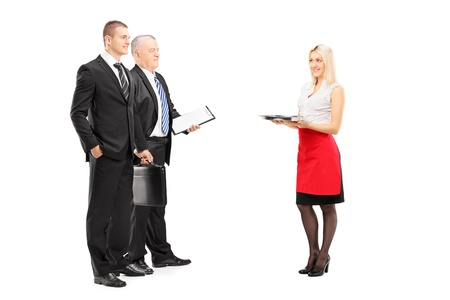Full length portrait of a smiling blond waitress with tray serving two businessmen isolated on white background photo