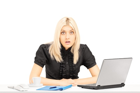 horrified: Surpised blond woman sitting on a table in her office, isolated on white background