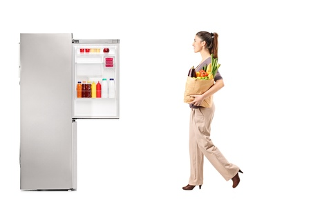 fridge: Full length portrait of a female with paper bag full of groceries walking towards refrigerator isolated on white background