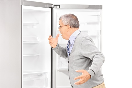finding out: Shocked mature man looking in empty fridge and finding out there is no food, isolated on white background Stock Photo