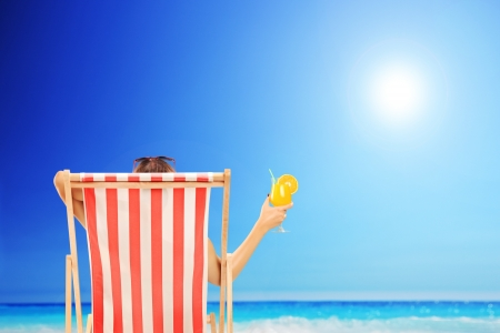 relaxando: Mulher em uma cadeira de praia curtindo o sol com um cocktail na m
