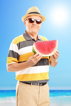 Mature gentleman holding a slice of watermelon on a beach next to the sea  photo