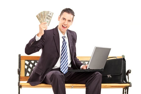 Happy businessman with laptop sitting on a wooden bench and holding US dollars isolated on white background photo