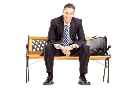 sitting on a bench: Smiling young businessman sitting on a wooden bench and looking at camera isolated on white background Stock Photo