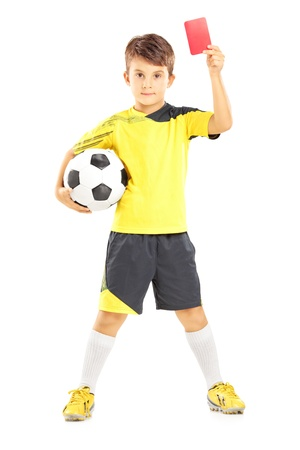 plimsoll: Full length portrait of a kid in sportswear holding soccer ball and giving red card isolated on white background