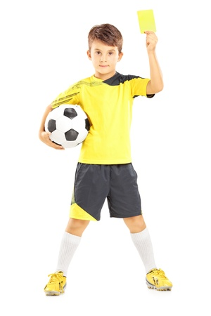 plimsoll: Full length portrait of a kid in sportswear holding soccer ball and giving yellow card isolated on white background Stock Photo
