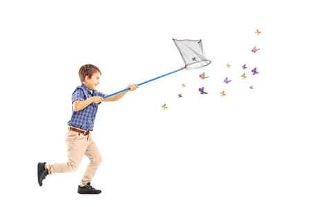 Retrato de cuerpo entero de un niño corriendo y cazando mariposas con una red aislada en el fondo blanco Foto de archivo - 21146074
