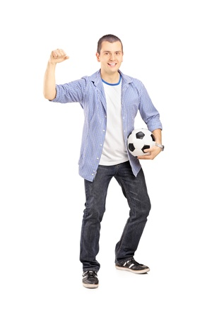 supporter: Full length portrait of an euphoric sport fan holding a soccer ball and cheering isolated on white background Stock Photo