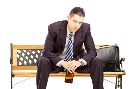 Disappointed young businessman sitting on a wooden bench with bottle in his hand isolated against white background photo
