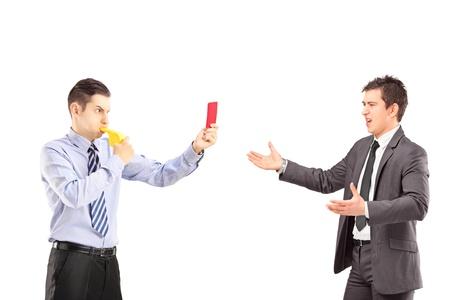 Man toont een rode kaart en een fluitje blazen om een jonge zakenman in pak, geïsoleerd op een witte achtergrond