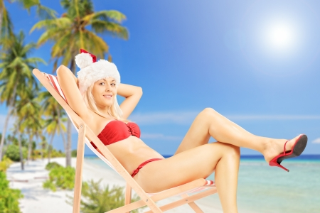 Young female in a santa costume sitting on a sun lounger on a tropical beach next to a sea photo