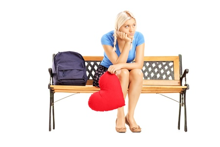 sitting on a bench: Disappointed blond female sitting on a wooden bench and holding a red heart isolated on white background