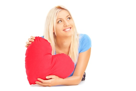 Smiling female lying down with red heart in her hands and wondering, isolated on white background photo