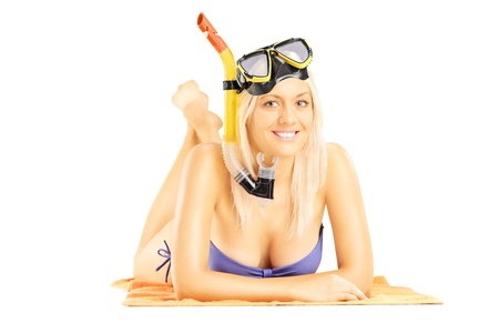 Young smiling female lying on a beach towel with a snorkeling mask isolated on white background photo