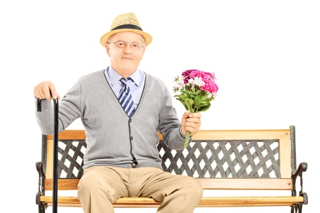 old man sitting: Senior gentleman sitting on a wooden bench and holding a bunch of flowers, isolated on white background Stock Photo