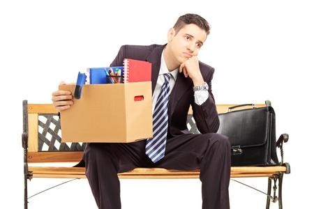 白い背景で隔離の所持品のボックス、ベンチに座っているスーツで失望した冗長若い男