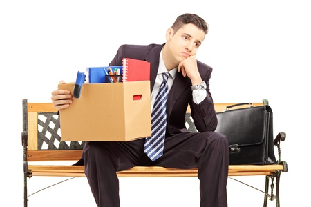 Disappointed redundant young man in a suit sitting on a bench with a box of belongings isolated on white background Фото со стока