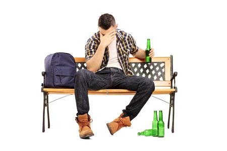 Drunk male teenager sitting on a bench and drinking beer isolated on white background  photo