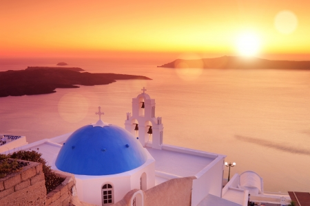 firostefani: Panoramic view of a blue dome of the church St. Spirou in Firostefani on the island of Santorini Greece, at sunset