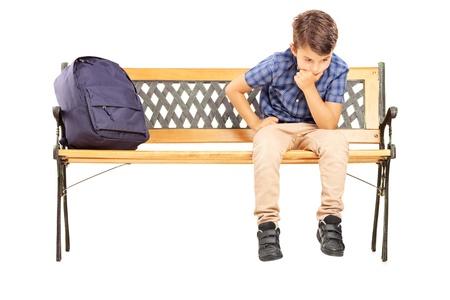 bambini pensierosi: Scuola ragazzo seduto su una panchina e il pensiero, isolato su sfondo bianco